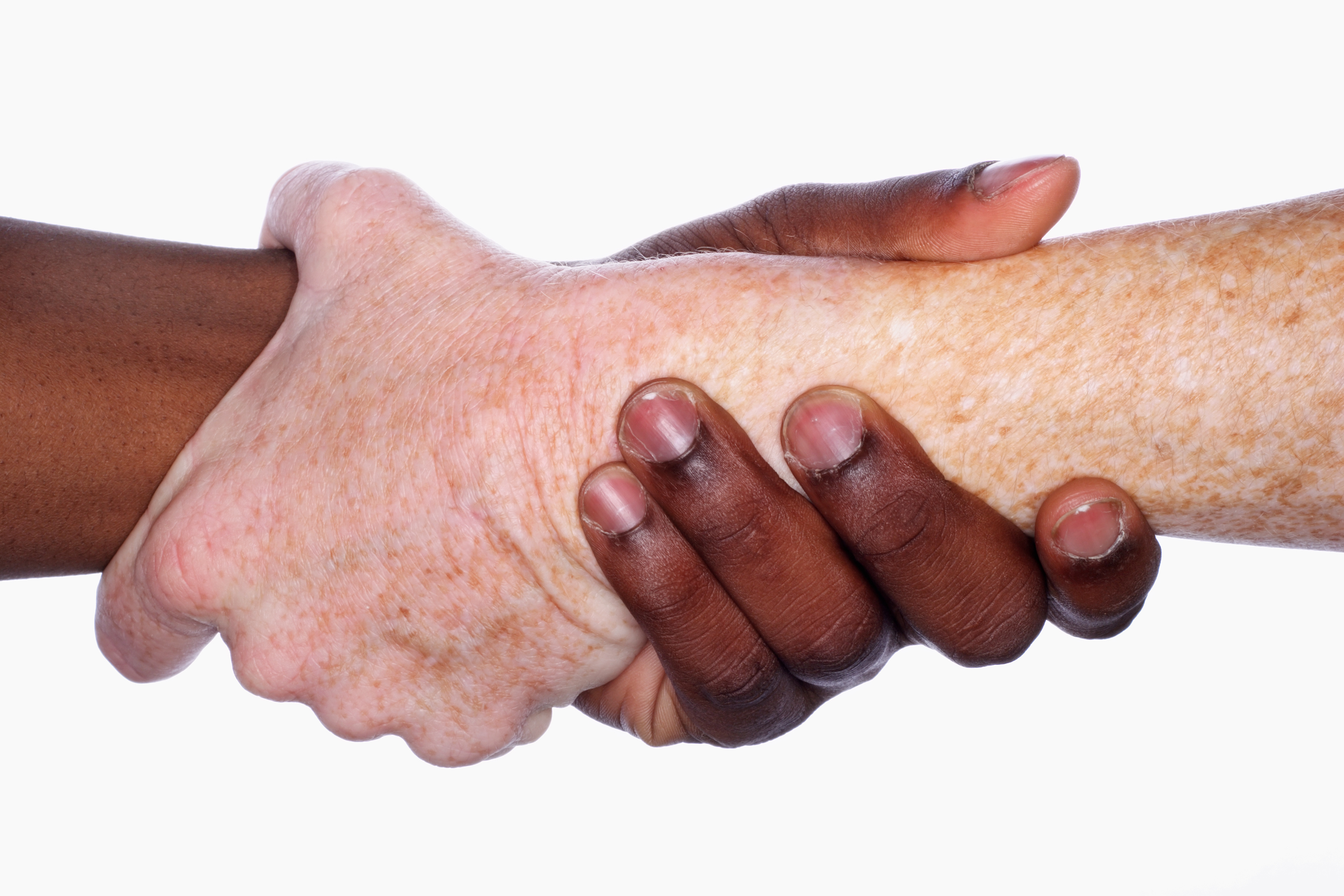 Two hands of different races grip each other in a handshake