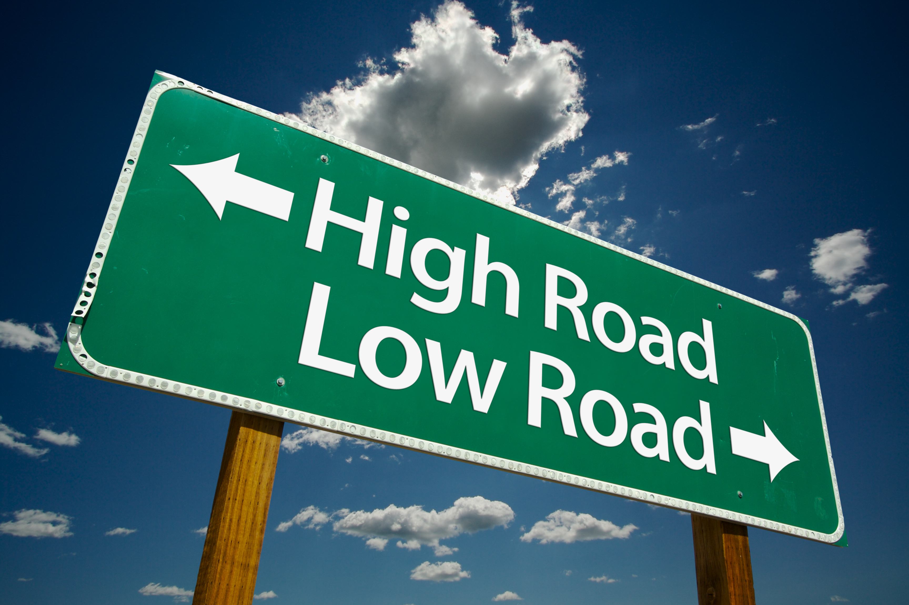"""""""High Road, Low Road"""" Road Sign with dramatic clouds and sky."""